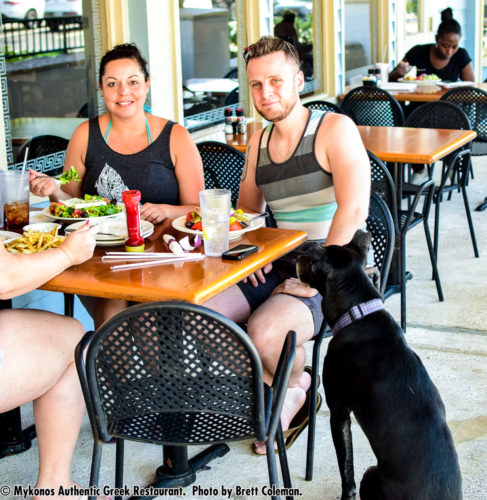 Photo of couple eating outside with black dog